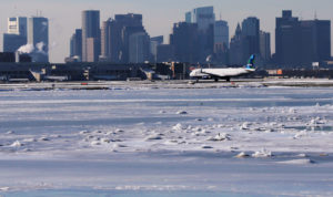 Ahead of an incoming winter snow storm, a Jet Blue flight waits to take off from Logan International Airport next to the frozen waters of the Atlantic Ocean harbour between Winthrop and Boston, Massachusetts, U.S., January 3, 2018. Photo by Brian Snyder/Reuters