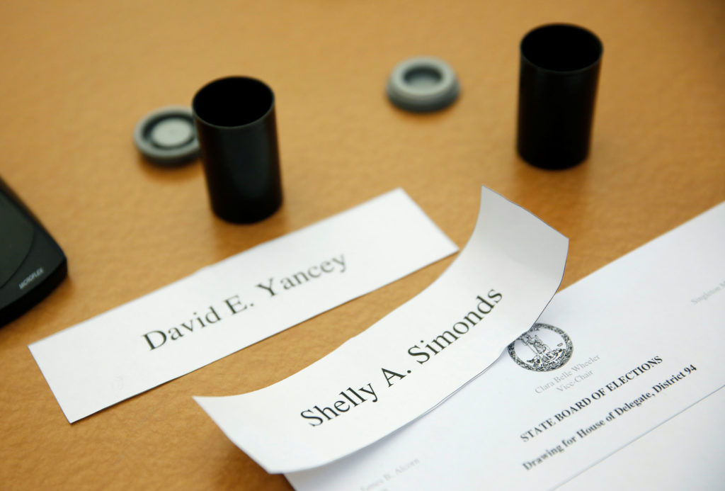 The names of Democrat Shelly Simonds and Republican incumbent Del. David Yancey are displayed along with film canisters before a random drawing by the Virginia Department of Elections to determine the winner of the 94th House of Delegates District Seat after a recount of the Nov. 7 election left the race a tie in Richmond, Virginia, U.S., January 4, 2018. REUTERS/Joshua Roberts - RC11EE65EEE0