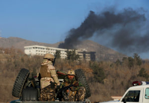 Afghan security forces keep watch as smoke rises from the Intercontinental Hotel in Kabul, Afghanistan. Photo by Omar Sobhani/Reuters