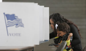 Betsy Argueta holds her daughter Isabella, 2, as she votes in the U.S. presidential election at the National Guard Armory in Smithfield, North Carolina, U.S. November 8, 2016. REUTERS/Chris Keane - HT1ECB81E6M72