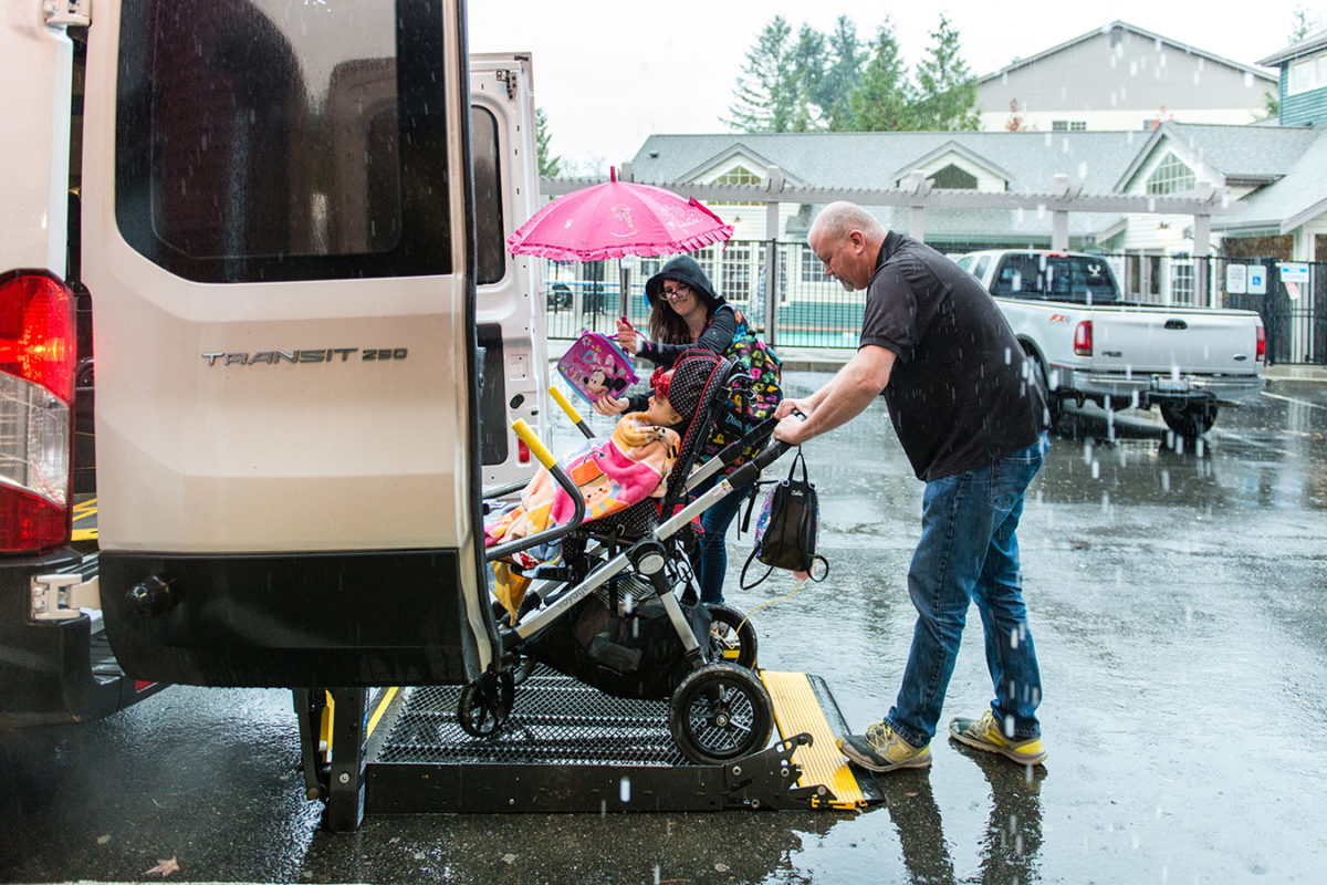 Driver Donavan Dunn loads Maddie Holt into the van on Nov. 21, 2017. The only way Maddie and her mother, Meagan Holt, can make the trip to the hospital is by using a service provided by Medicaid called non-emergency medical transportation, or NEMT. (Heidi de Marco/KHN)
