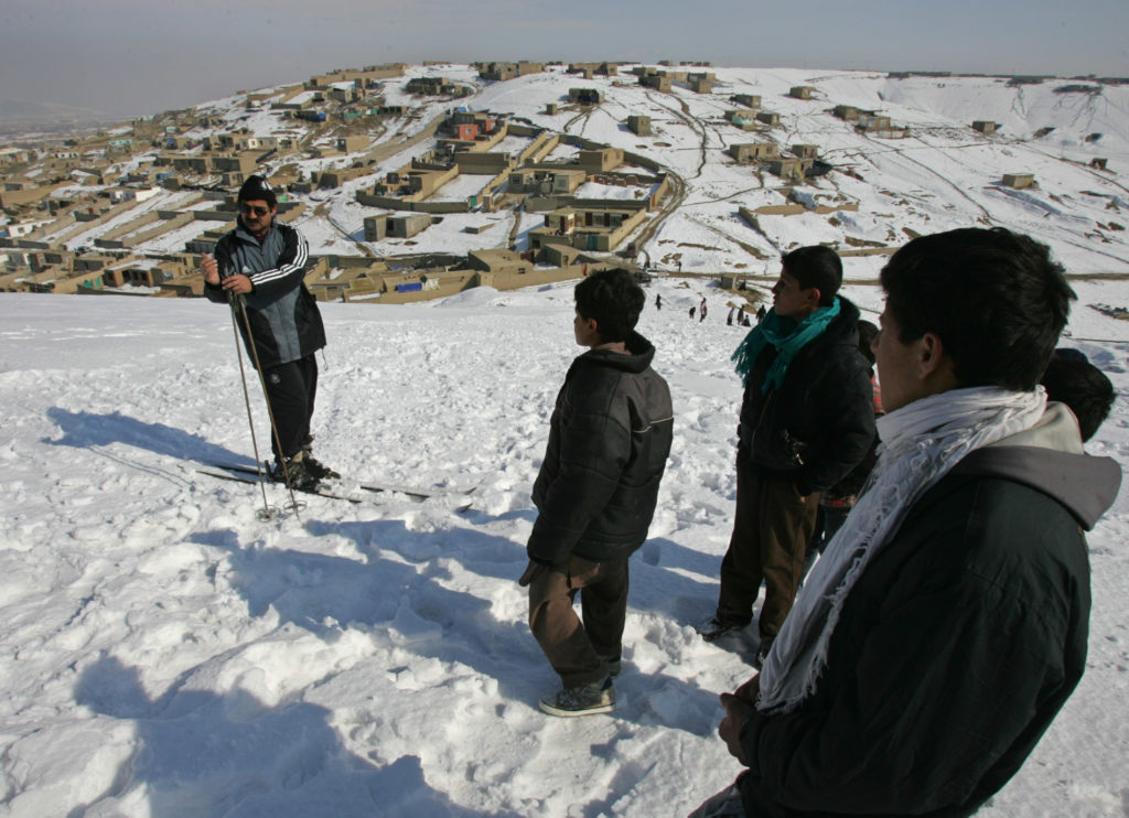 Afghan skier Hamayoon Kargar (L) explains the sport of skiing to people on a hill in Kabul, Afghanistan January 20, 2006. Kargar is a former Afghan champion skier who wants to revive the sport in his country after decades of war. REUTERS/Ahmad Masood - RP3DSFDQJDAC