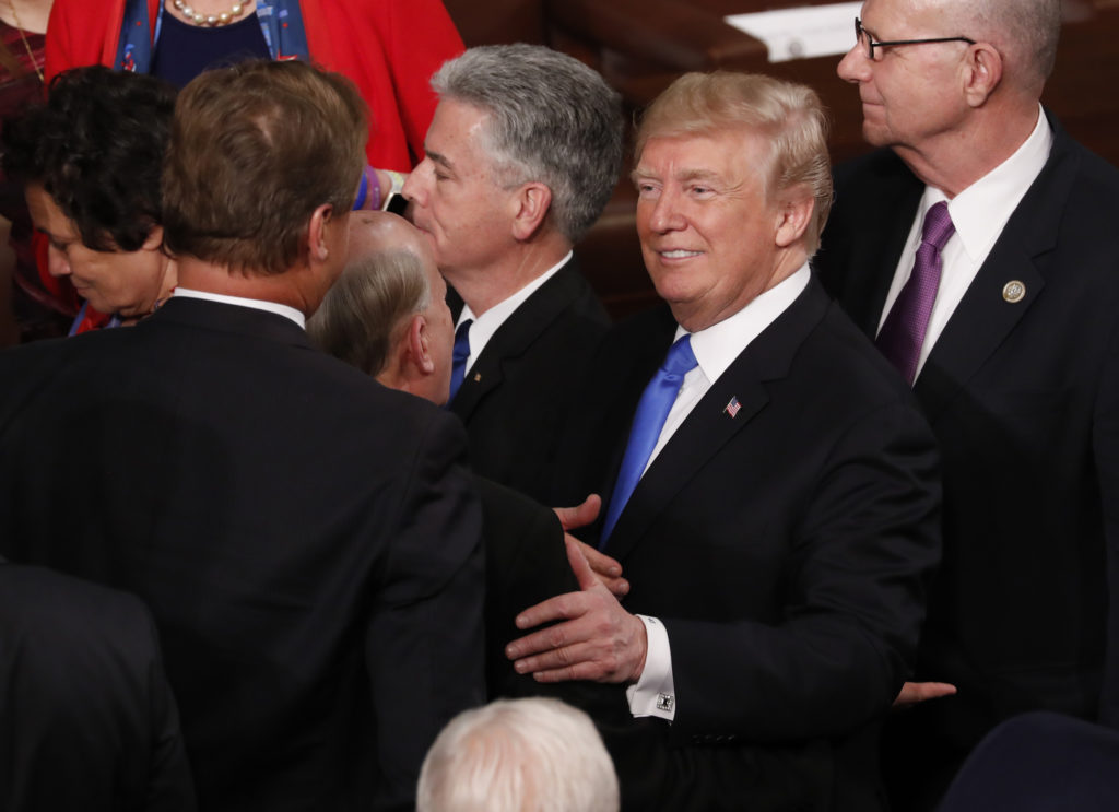 U.S. President Donald Trump (R) talks with members of Congress as he departs after delivering his State of the Union addre...