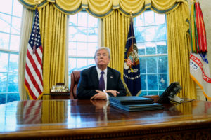 U.S. President Donald Trump sits at his desk after signing directives to impose tariffs on imported washing machines and solar panels in the Oval Office at the White House in Washington, U.S., January 23, 2018. REUTERS/Jonathan Ernst - RC165DD26990