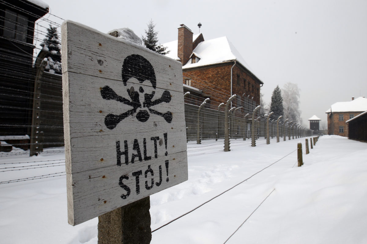 """A sign that reads """"Stop"""" placed near a barb wire is seen at the concentration camp during a ceremony marking the 68th anniversary of the liberation of the Auschwitz by Soviet troops and to remember the victims of the Holocaust, in Auschwitz Birkenau January 27, 2013 . REUTERS/Peter Andrews (POLAND - Tags: POLITICS ANNIVERSARY) - GM1E91R1KD201"""