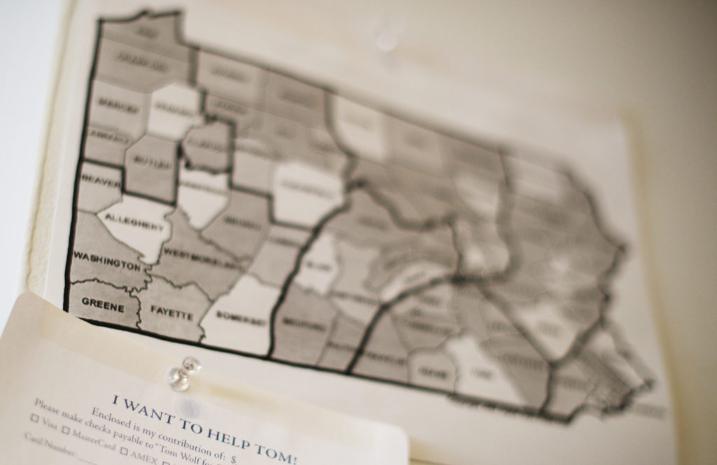 a donation envelope and a map of counties in pennsylvania is displayed on a wall at