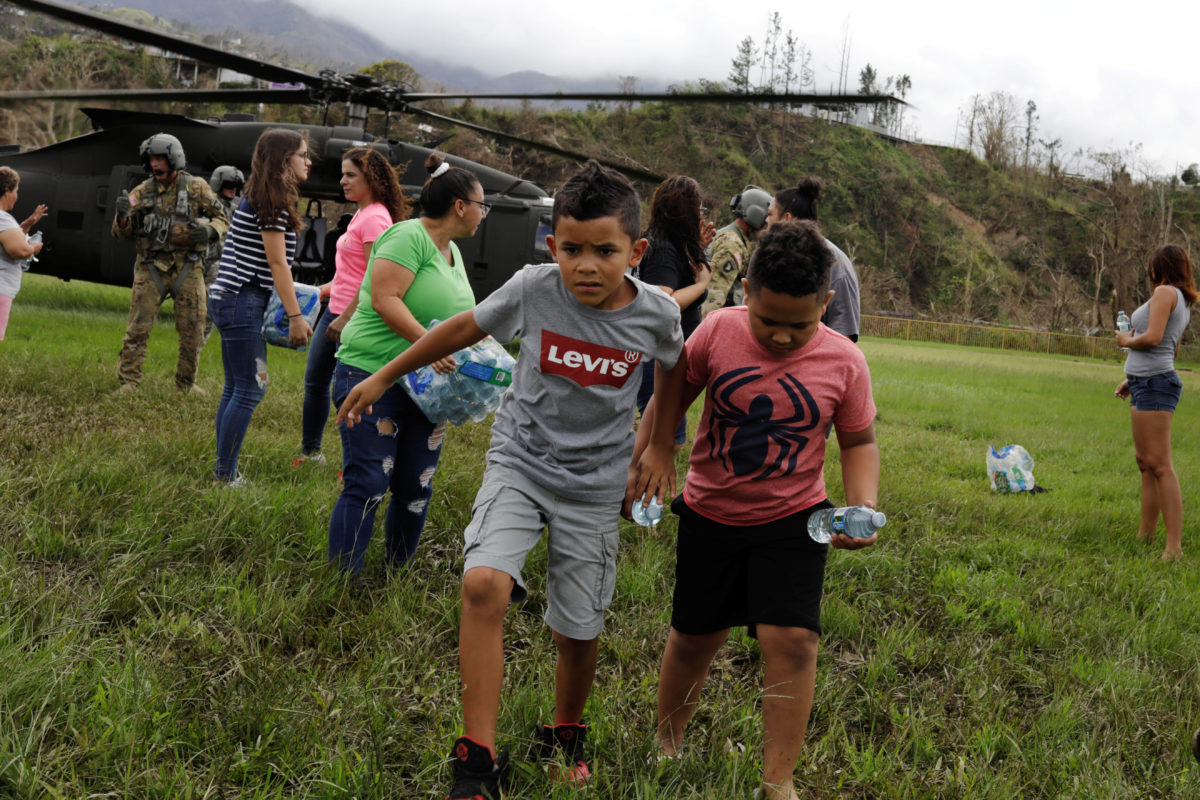 """Boys carry water away from an HH-60 Blackhawk helicopter after soldiers working with the U.S. Army's 101st Airborne Division's """"Dustoff"""" unit dropped off relief supplies during recovery efforts in October following Hurricane Maria, in Jayuya, Puerto Rico. Photo by Lucas Jackson/Reuters"""