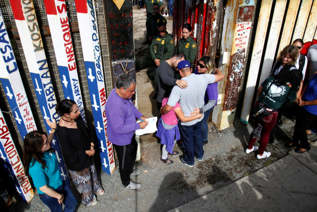 U.S. Border patrol agents open a single gate to allow families to hug and talk along the Mexico and U.S border in Tijuana,...