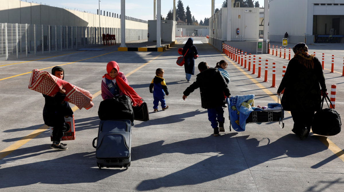 A Syrian woman carries a cradle with his son as she and her children walk through the border gate to cross into the Syrian town of Jarablus, from Karkamis, Turkey. Photo by Umit Bektas/Reuters