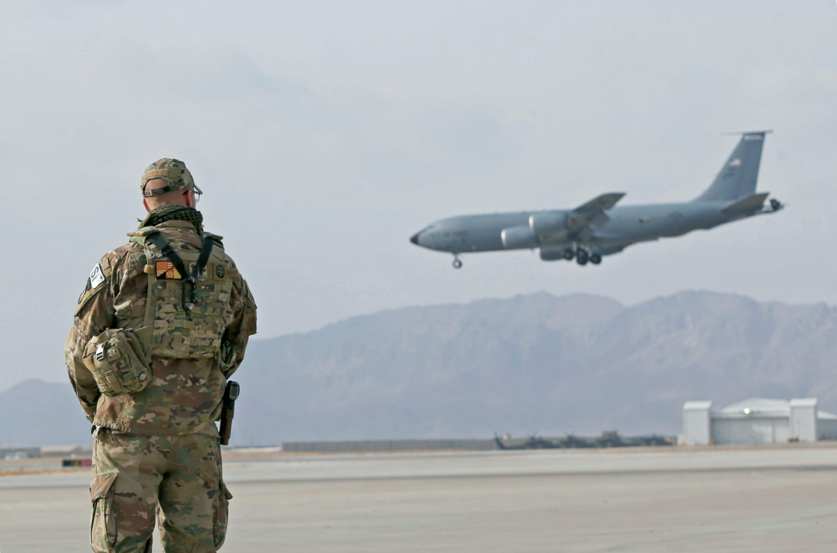 U.S. service member stands guard as an U.S. military transport plane lands at the Kandahar air base, Afghanistan January 23, 2018. Photo by Omar Sobhani/Reuters