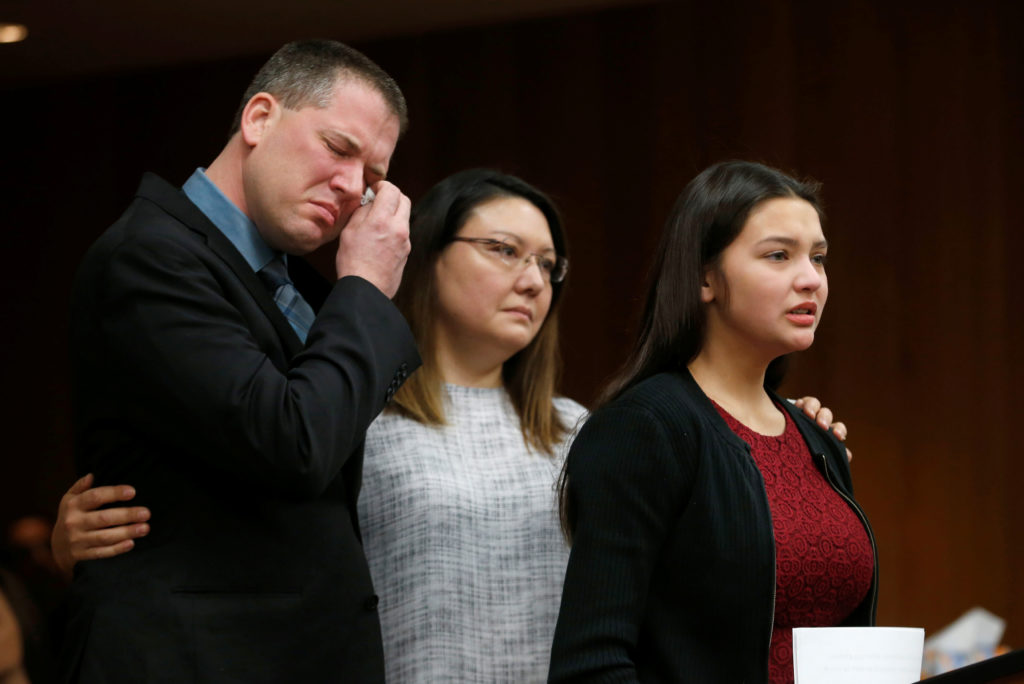 Ashleigh Weiszerbod reads her victim impact statement as her parents stand with her during the sentencing hearing of Larry Nassar, a former team USA Gymnastics doctor who pleaded guilty in November 2017 to sexual assault charges, in the Eaton County Court in Charlotte, Michigan, U.S., February 2, 2018. REUTERS/Rebecca Cook - RC19258EDF40