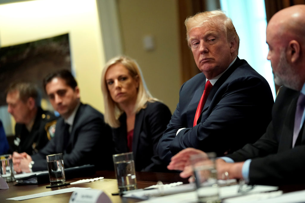 U.S. President Donald Trump, flanked by Secretary of Homeland Security Kirstjen Nielsen (C), meets with members of Congress and U.S. law enforcement about crime and immigration issues, specifically the MS-13 gang, at the White House in Washington, U.S. February 6, 2018. REUTERS/Jonathan Ernst - RC176E856DF0