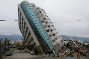 Rescue workers are seen by a damaged building after an earthquake hit Hualien, Taiwan. Photo by Reuters