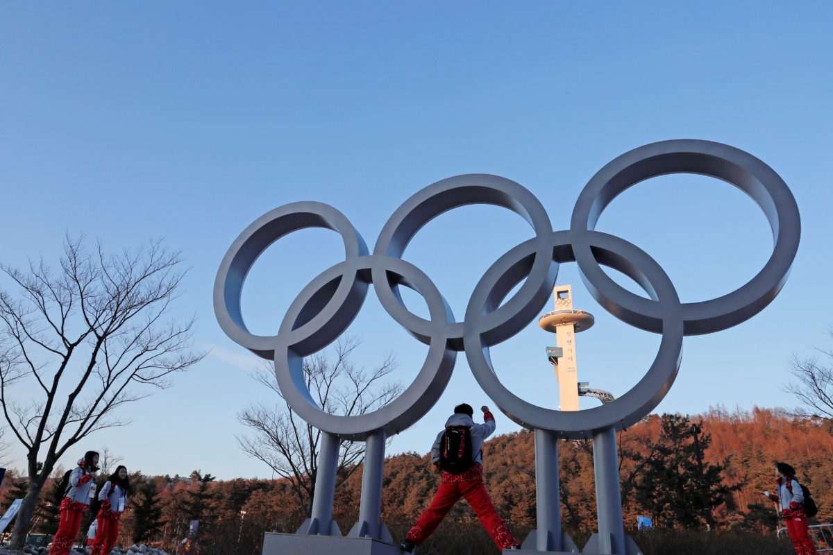 Volunteers pose next to the Olympic rings at the Pyeongchang Winter Olympic Games in Pyeongchang, South Korea. Photo by Jorge Silva/Reuters