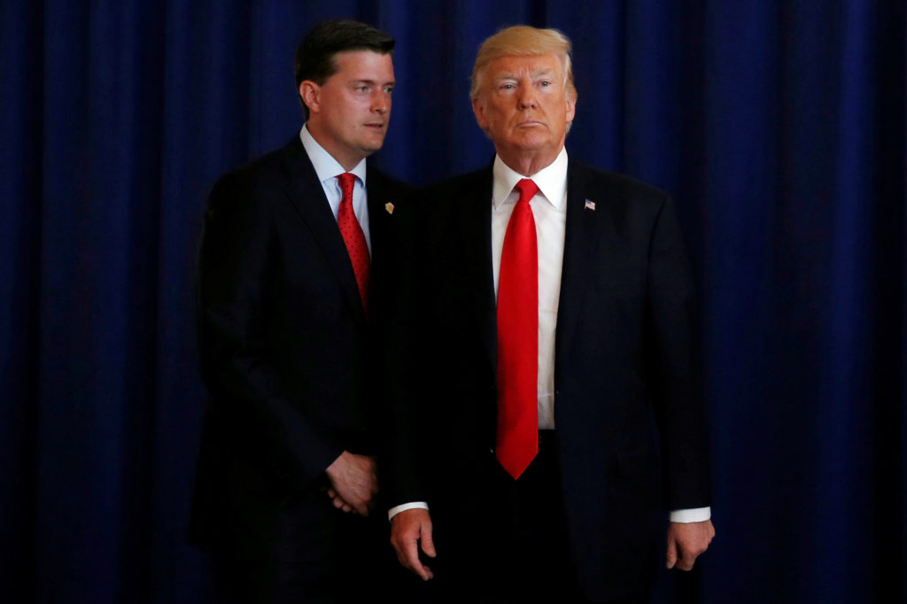White House Staff Secretary Rob Porter (L) reminds U.S. President Donald Trump he had a bill to sign after he departed quickly following remarks at his golf estate in Bedminster, New Jersey U.S., August 12, 2017. Picture taken August 12, 2017. REUTERS/Jonathan Ernst - RC135A06B980
