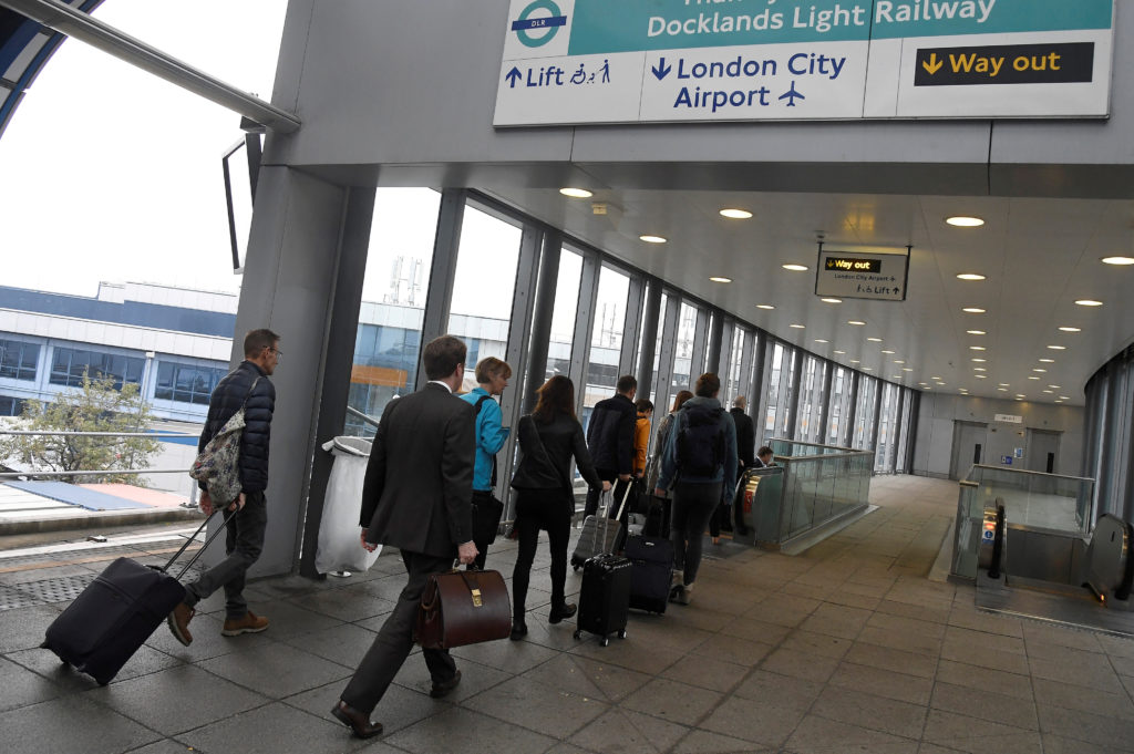 Passengers alight from a train to enter City Airport in London. Photo by Toby Melville/Reuters