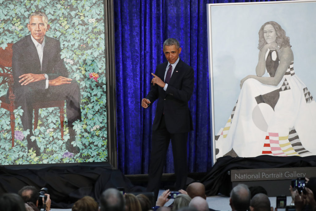 Former President Barack Obama stands between painted portraits of himself and that of former first lady Michelle Obama during an unveiling ceremony at the Smithsonian's National Portrait Gallery in Washington, D.C. Photo by Jim Bourg/Reuters