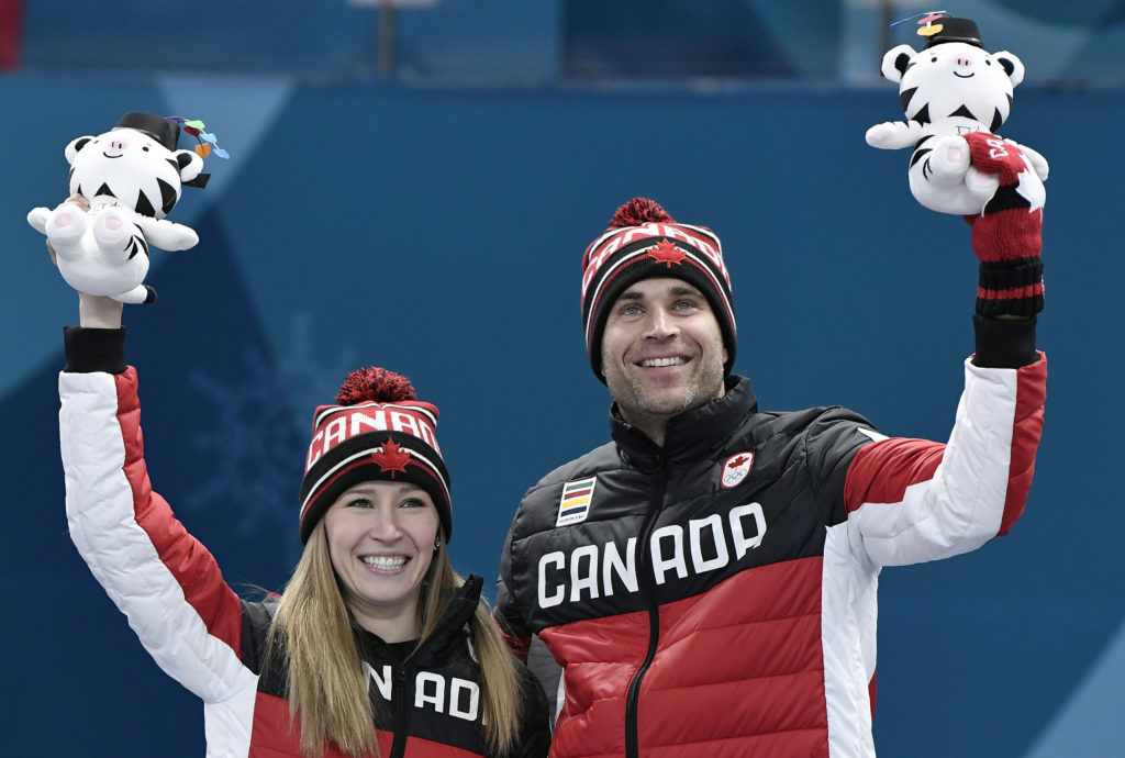 Gold medalists Kaitlyn Lawes and John Morris of Canada celebrate during the victory ceremony at the 2018 Winter Games. Photo by Toby Melville/Reuters