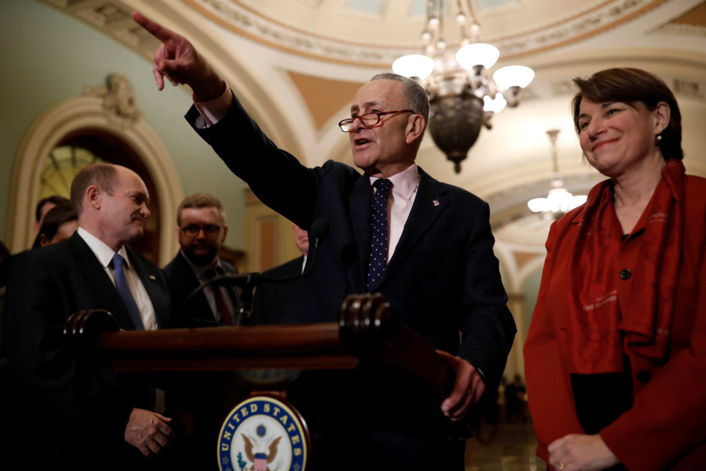 Senate Minority Leader Chuck Schumer, accompanied by Sen. Chris Coons (D-Del) and Sen. Amy Klobuchar (D-Minn.), speaks with reporters following the weekly policy luncheons at the U.S. Capitol in Washington, D.C. Photo by Aaron P. Bernstein/Reuters
