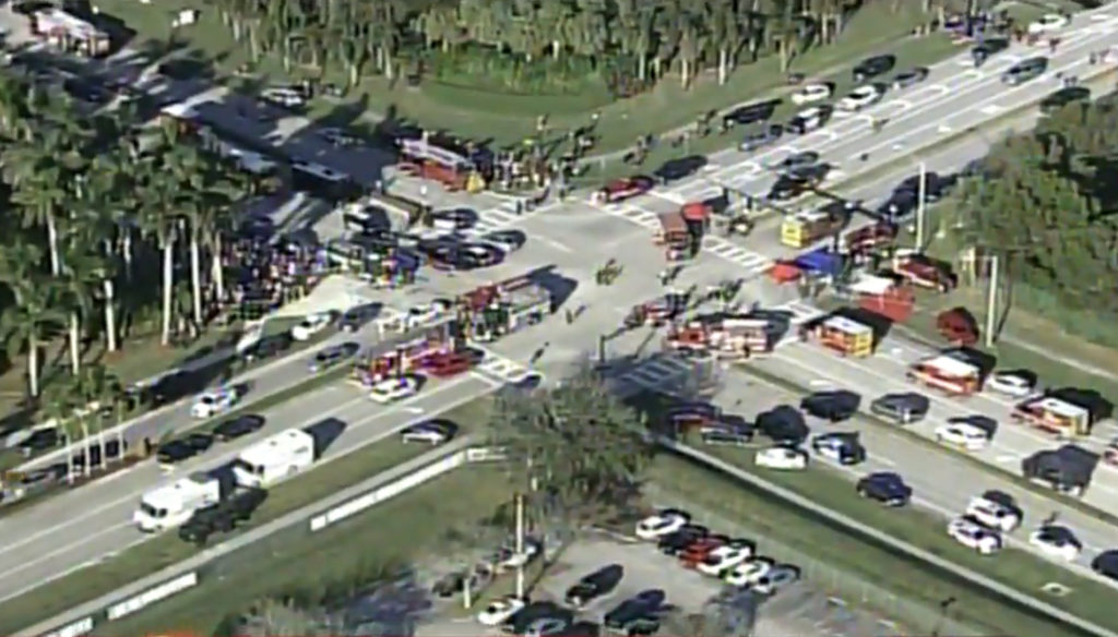 Police and rescue workers attend the scene near Marjory Stoneman Douglas High School following a shooting incident in Parkland, Florida, in a still image taken from a video.  Image courtesy of WSVN.com via Reuters