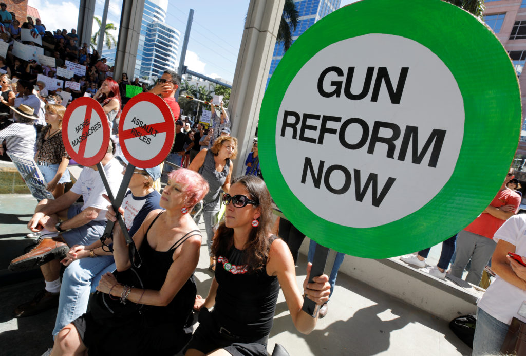 Protesters hold signs as they call for a reform of gun laws three days after the shooting at Marjory Stoneman Douglas High School, at a rally in Fort Lauderdale, Florida, U.S., February 17, 2018. REUTERS/Jonathan Drake.