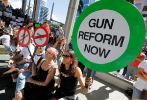 Protesters hold signs as they call for a reform of gun laws three days after the shooting at Marjory Stoneman Douglas High School, at a rally in Fort Lauderdale, Florida, U.S., February 17, 2018. REUTERS/Jonathan Drake - RC162B87E510