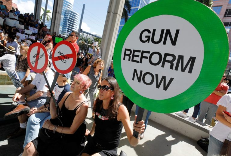 Protesters hold signs as they call for a reform of gun laws three days after the shooting at Marjory Stoneman Douglas High School, at a rally in Fort Lauderdale, Florida, U.S., February 17, 2018. REUTERS/Jonathan Drake