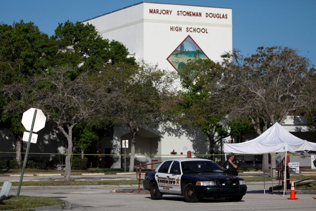 A police officer Jamie Rubenstein stands guard in front of the Marjory Stoneman Douglas High School, after the police secu...