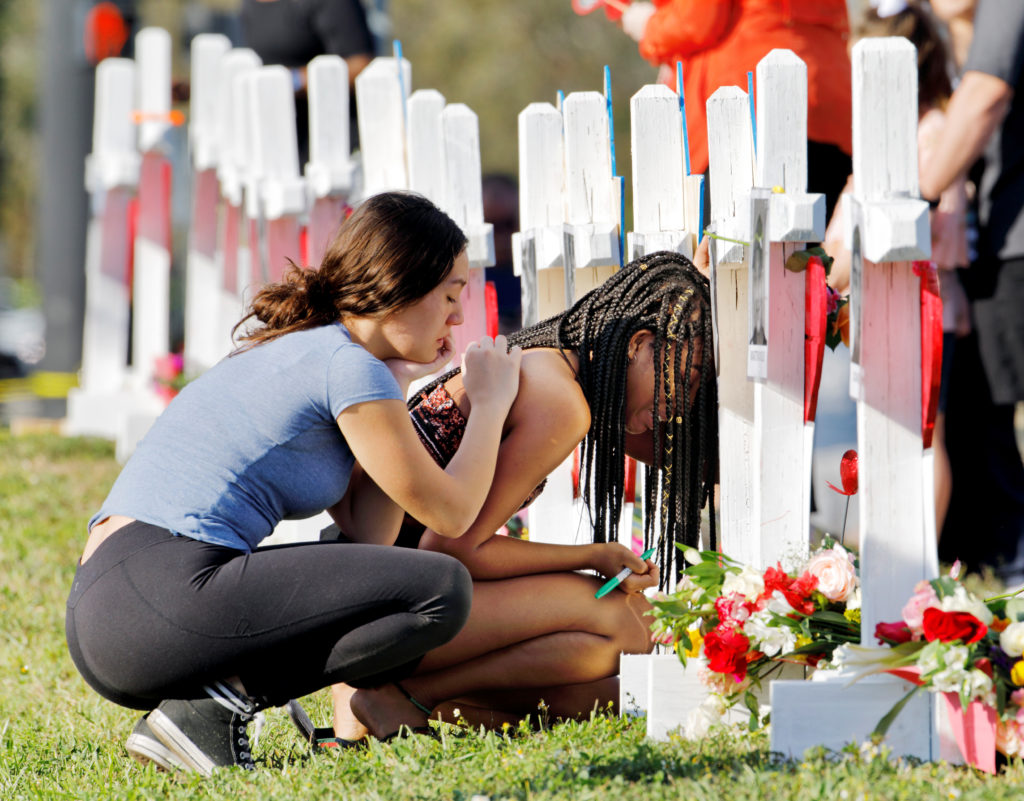 A senior at Marjory Stoneman Douglas High School weeps in front of a cross and Star of David for shooting victim Meadow Pollack while a fellow classmate consoles her at a memorial by the school in Parkland, Florida, U.S. February 18, 2018. REUTERS/Jonathan Drake