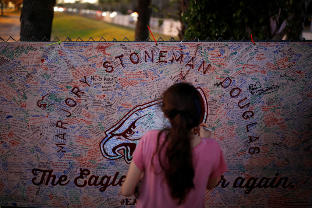 A girl writes a note on a banner placed on the fence of the Marjory Stoneman Douglas High School to commemorate the victims of the mass shooting, in Parkland, Florida. Photo by Carlos Garcia Rawlins/Reuters