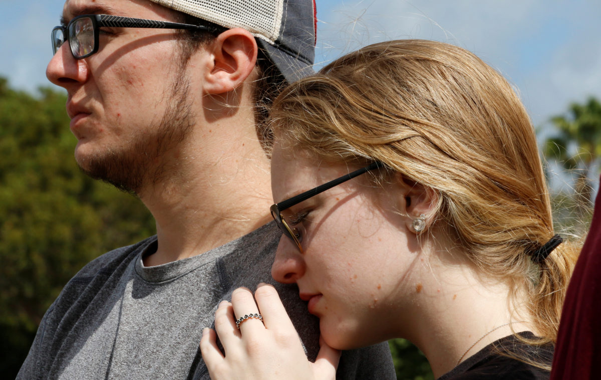 Former Marjory Stoneman Douglas High School student Madisyn Coles leans on the shoulder of an unidentified friend as they view memorials on a fence surrounding the school in Parkland, Florida, U.S., February 23, 2018. REUTERS/Joe Skipper - RC13D1F70000