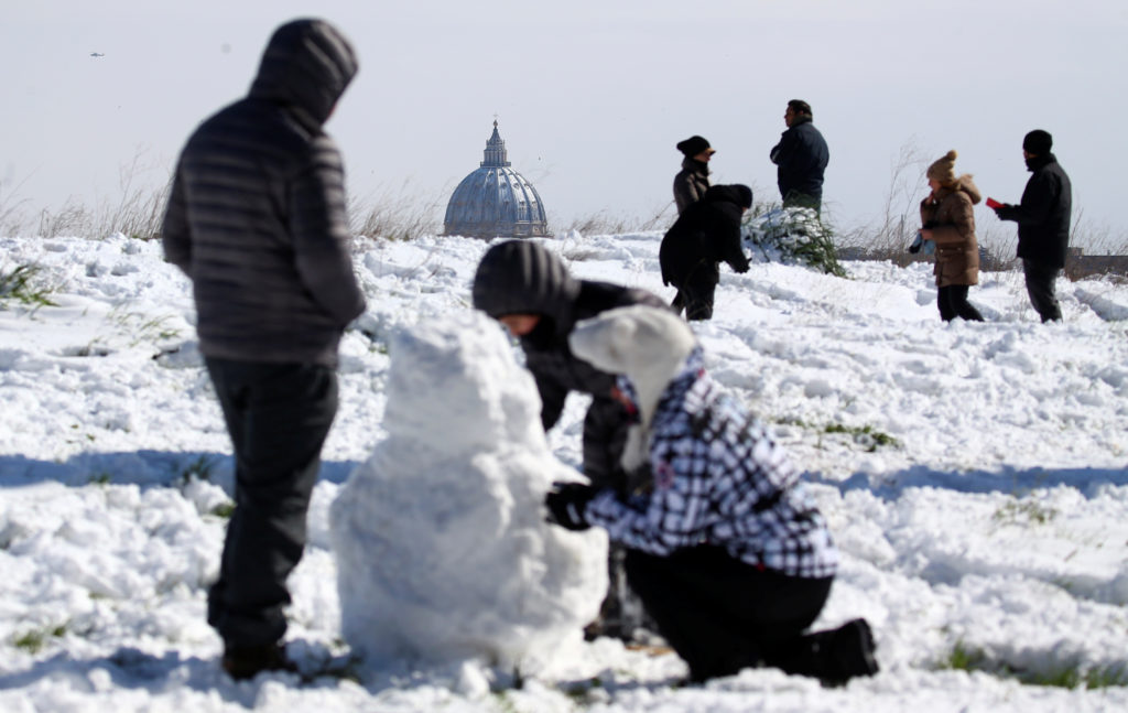 Saint Peter's Basilica is seen in the background as people enjoy the snow in Rome, Italy on Feb. 26. Photo by Alessandro Bianchi/Reuters