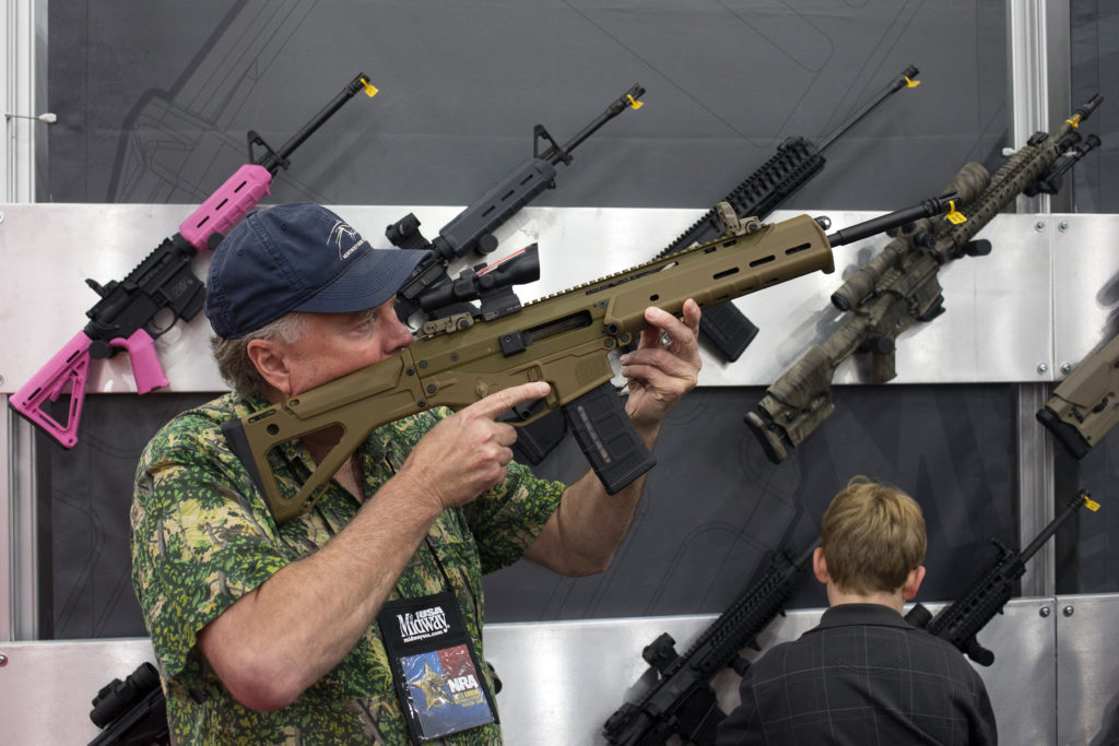 A man takes aim with an assault rifle at an exhibit booth at the George R. Brown convention center, the site for the Natio...