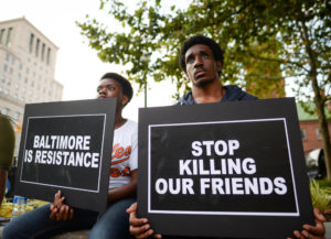 Jaz Jacobs (L) and Kevin Walloons gather to remember Freddie Gray and all victims of police violence during a rally outside city hall in Baltimore, Maryland, U.S., July 27, 2016. REUTERS/Bryan Woolston - S1BETSBQDAAA