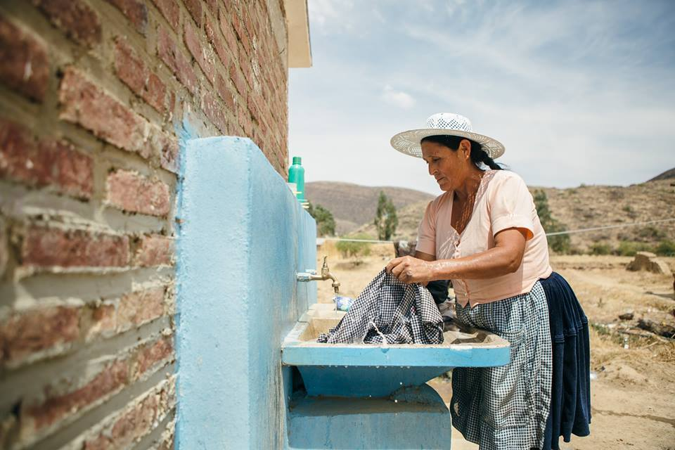 A woman in Arani district in rural Bolivia washes her clothes in a newly constructed clean water system. Photo courtesy of Water For People