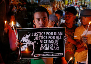 Protesters and residents hold lighted candles and placards at the wake of Kian Loyd delos Santos, a 17-year-old high school student, who was among the people shot dead last week in an escalation of President Rodrigo Duterte's war on drugs in Caloocan city, Metro Manila, Philippines August 25, 2017. REUTERS/Dondi Tawatao - RC1B6C8527A0