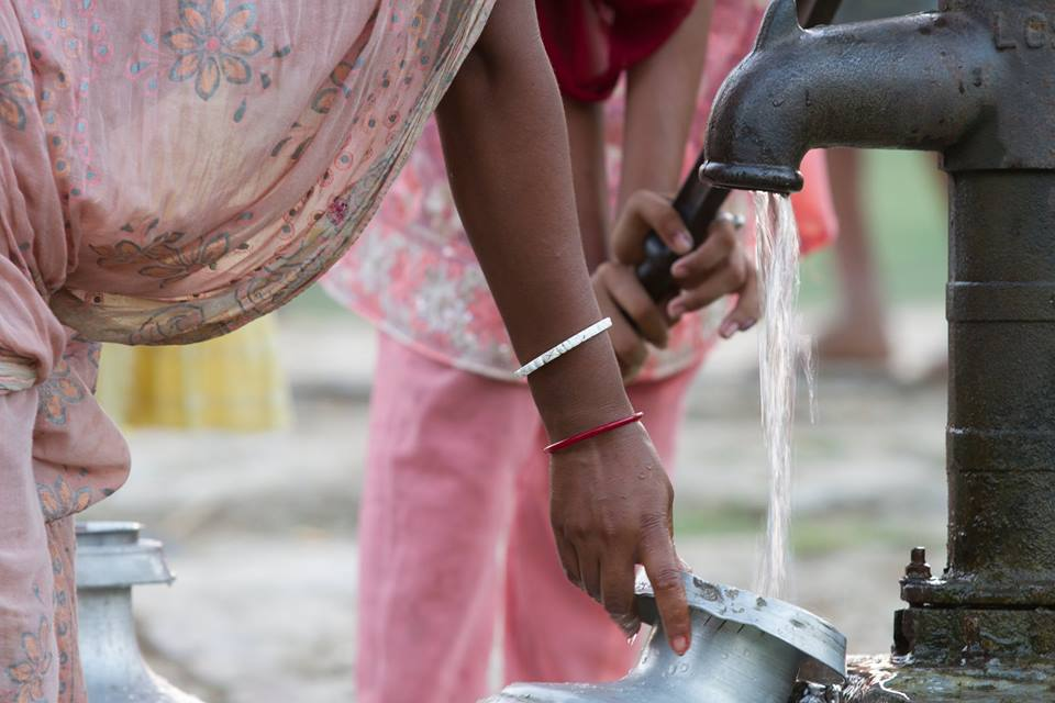 In India, the most common drinking water system is a well with a hand pump on top. People fill containers with water and use the drinking water at home. Photo courtesy of Water For People