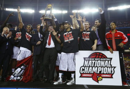 Louisville Cardinals head coach Rick Pitino holds up the trophy as he and his team celebrate after defeating the Michigan Wolverines in their NCAA men's Final Four championship basketball game in Atlanta, Georgia April 8, 2013. REUTERS/Jeff Haynes (UNITED STATES - Tags: SPORT BASKETBALL TPX IMAGES OF THE DAY) - TB3E9490BOPNP