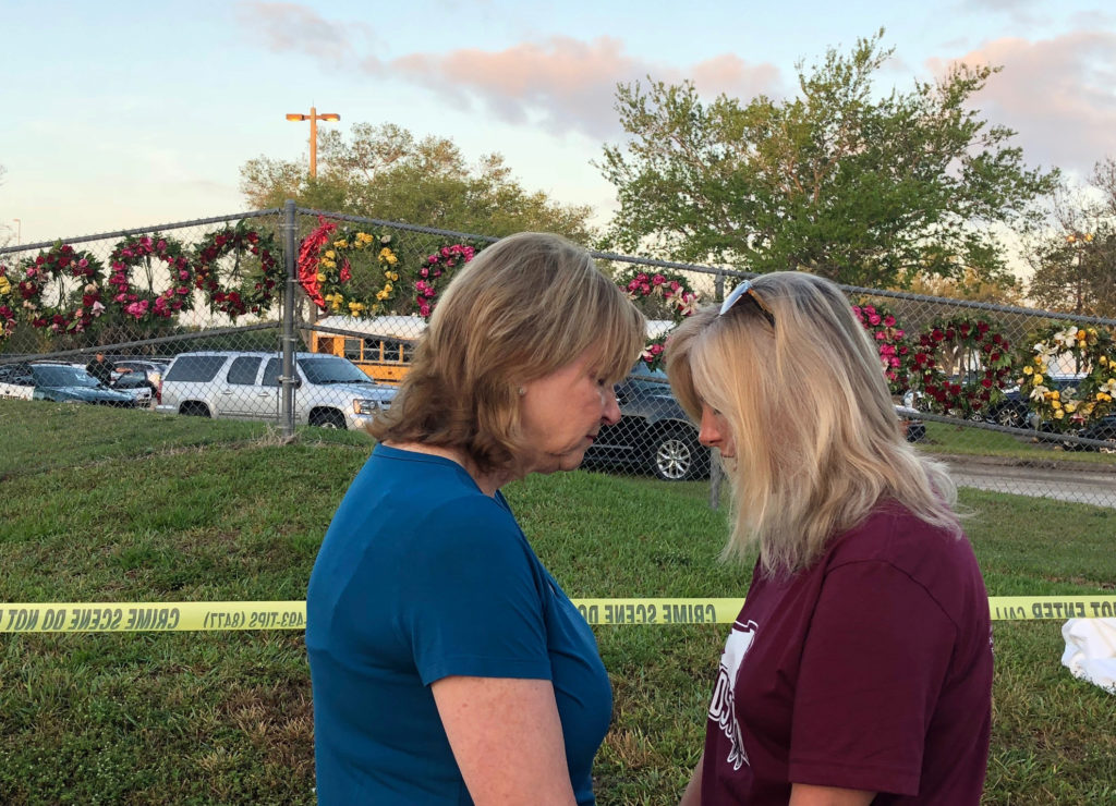 Beverly Turner and Michele Brown huddle to pray in front of a chain-link fence decorated with wreaths as students and faculty arrive at Marjory Stoneman Douglas High School for the first time since the mass shooting in Parkland, Florida, U.S., February 28, 2018. Photo by Bernie Woodall/REUTERS