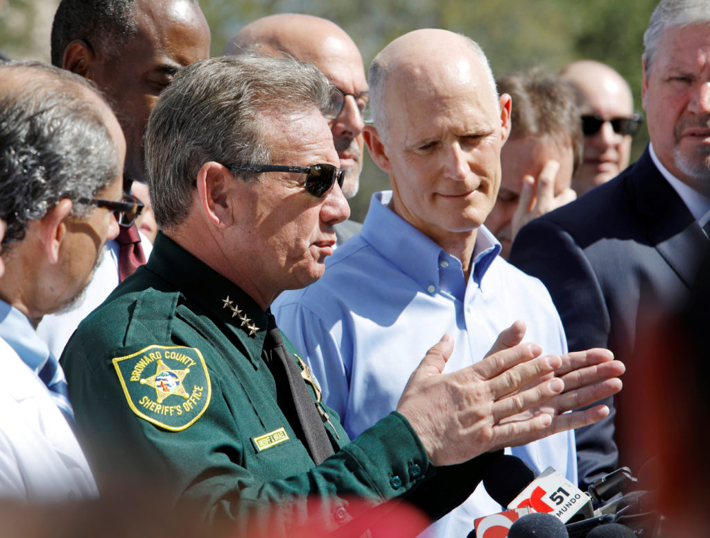 Broward County Sheriff Scott Israel speaks to the media while Florida Governor Rick Scott listens outside Marjory Stoneman Douglas High School one day after a shooting at the school left 17 dead, in Parkland, Florida, U.S., February 15, 2018. REUTERS/Jonathan Drake - RC1AB3EA6CF0