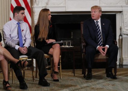 Marjory Stoneman Douglas High School shooting surviving students Jonathan Blank (L) and Julia Cordover (C) listen to U.S. President Donald Trump speak during a listening session with high school students and teachers to discuss school safety and guns at the White House in Washington, U.S., February 21, 2018 REUTERS/Jonathan Ernst - HP1EE2L1OFLHP
