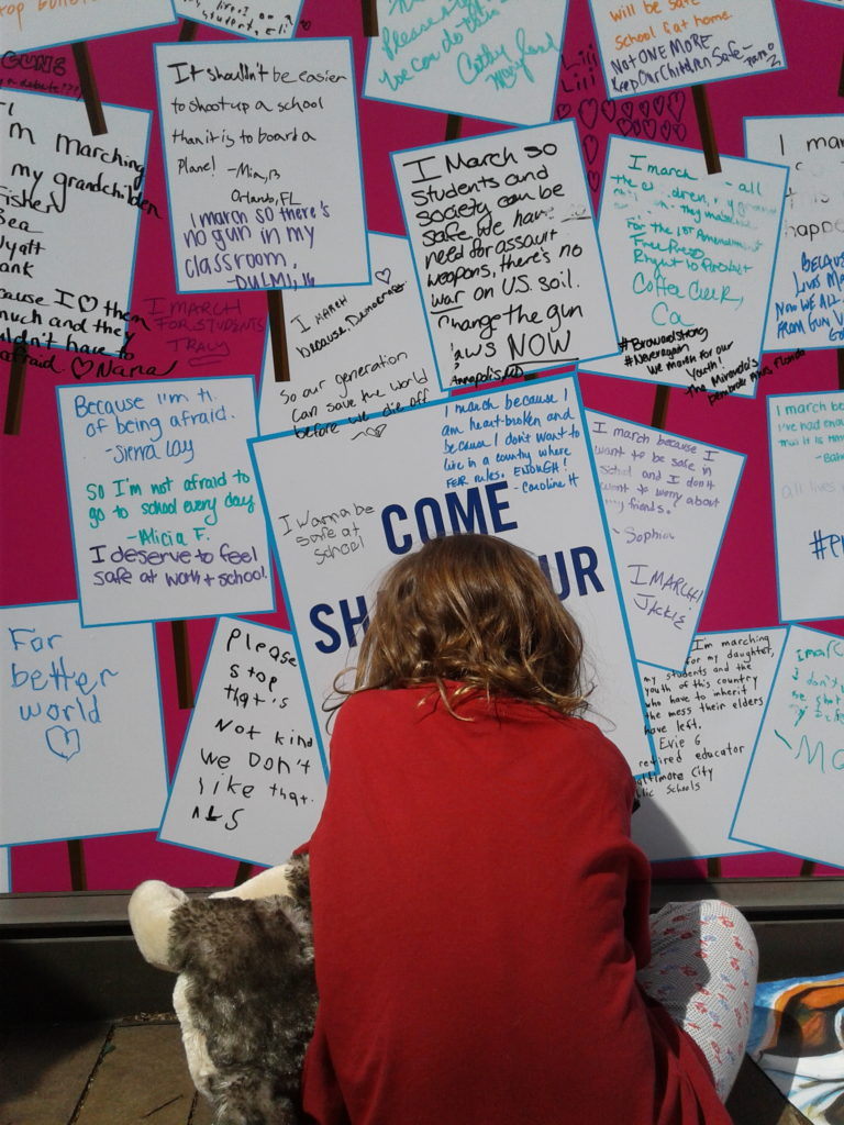 A young girl signs a wall at in Washington, D.C. during the March for Our Lives on Saturday, March 24. Photo by Michael Rios