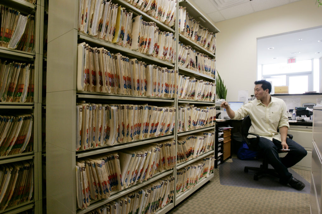 Medical records occupy considerable space at Dr. Ingrid Chung's practice where the office manager Dan Kim (R) manages the front office in Chantilly, Virginia, July 30, 2009. One of the stated U.S. healthcare overhaul objectives of U.S. President Barack Obama includes electronic record keeping and billing to reduce costs among others. REUTERS/Hyungwon Kang
