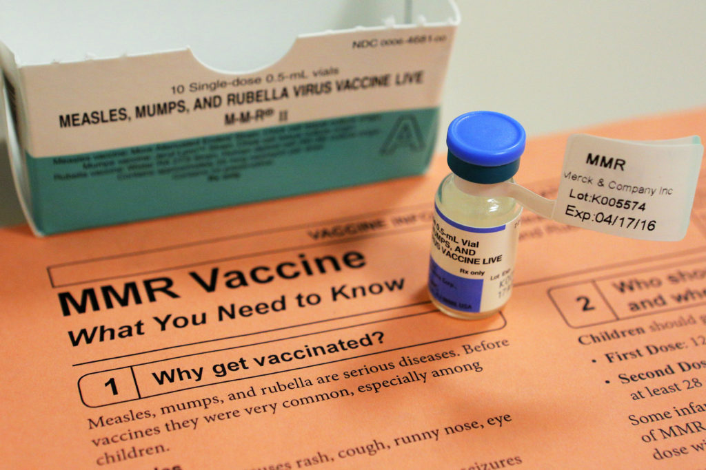 A vial of measles, mumps and rubella vaccine and an information she…