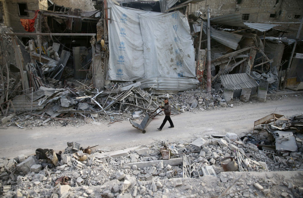 A man pushes a cart past damaged buildings at the besieged town of Douma, Syria. Photo by Bassam Khabieh/Reuters