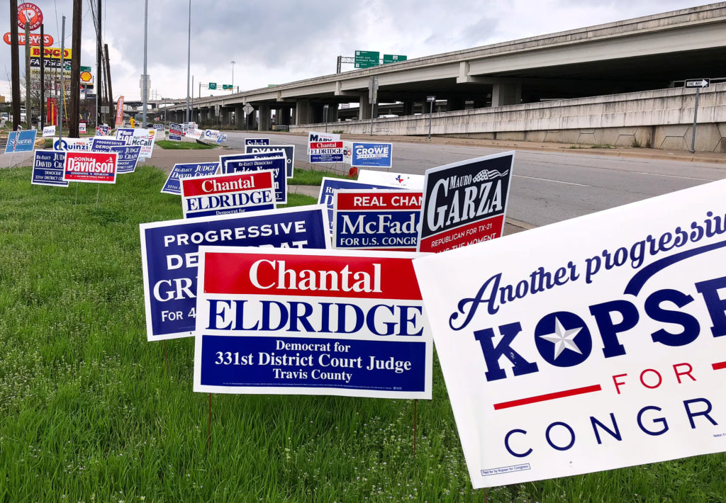 Political campaign signs stand outside a polling station in Austin ahead of the first statewide primary in 2018. Photo by Jon Herskovitz/Reuters