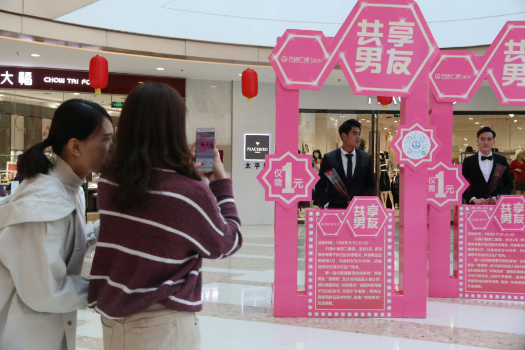 "A woman takes pictures of men standing behind booths during an International Women's Day event inside a shopping mall, where customers can rent a ""boyfriend"" for 30 minutes with one yuan ($0.16), in Binzhou, Shandong province, China. Photo by Reuters"