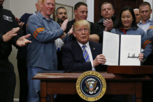 President Donald Trump holds up a proclamation during a White House ceremony to establish tariffs on imports of steel and aluminum at the White House in Washington, D.C. Photo by Leah Millis/Reuters