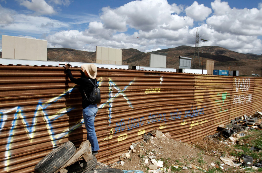 A tourist looks on near prototypes of President Donald Trump's border wall with Mexico behind the current border fence in this picture taken from the Mexican side of the border in Tijuana, Mexico. Photo by Jorge Duenes/Reuters