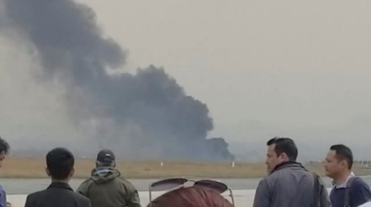 People stand as smoke rises following the crash of a Bangladeshi aircraft at Kathmandu airport, Nepal, in this picture grab obtained from social media video. Photo by NITIN KEYAL/via Reuters